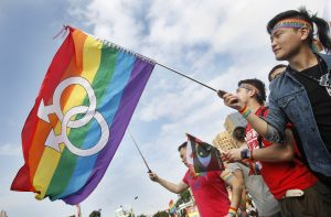 Taiwanese gay rights activist waves a rainbow equality flag.