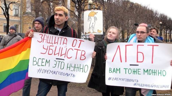 """LGBTQ rights activists in St. Petersburg bring allegations of an anti-gay purge in Chechnya. The sign on the left says, """"Everyone needs protection from murders."""" The banner on the right reads, """"LGBT.It could happen to you too."""""""